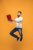 Jump of young man over orange studio background using laptop computer while jumping.