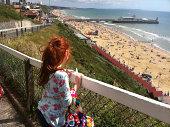 Photo of a little girl looking from a cliff at Bournemouth beach