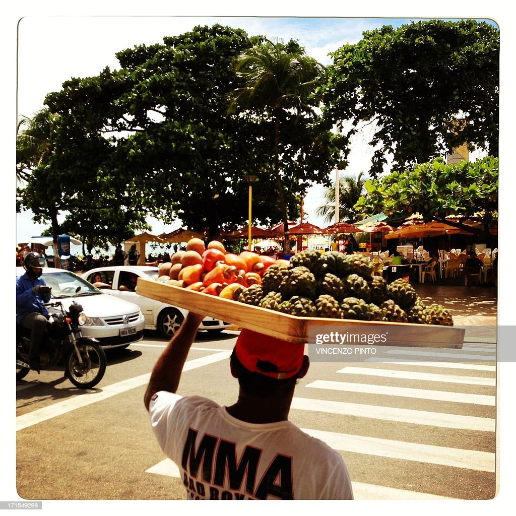 Image taken with a mobile phone showing a street fruit seller during the FIFA Confederations Cup Brazil 2013 in Fortaleza, on June 25, 2013. Attention editors : this image is part of a serie of pictures showing the backstage of the Confederation Cup competition and the daily life in Brazil as experienced by AFP photographers covering the event.