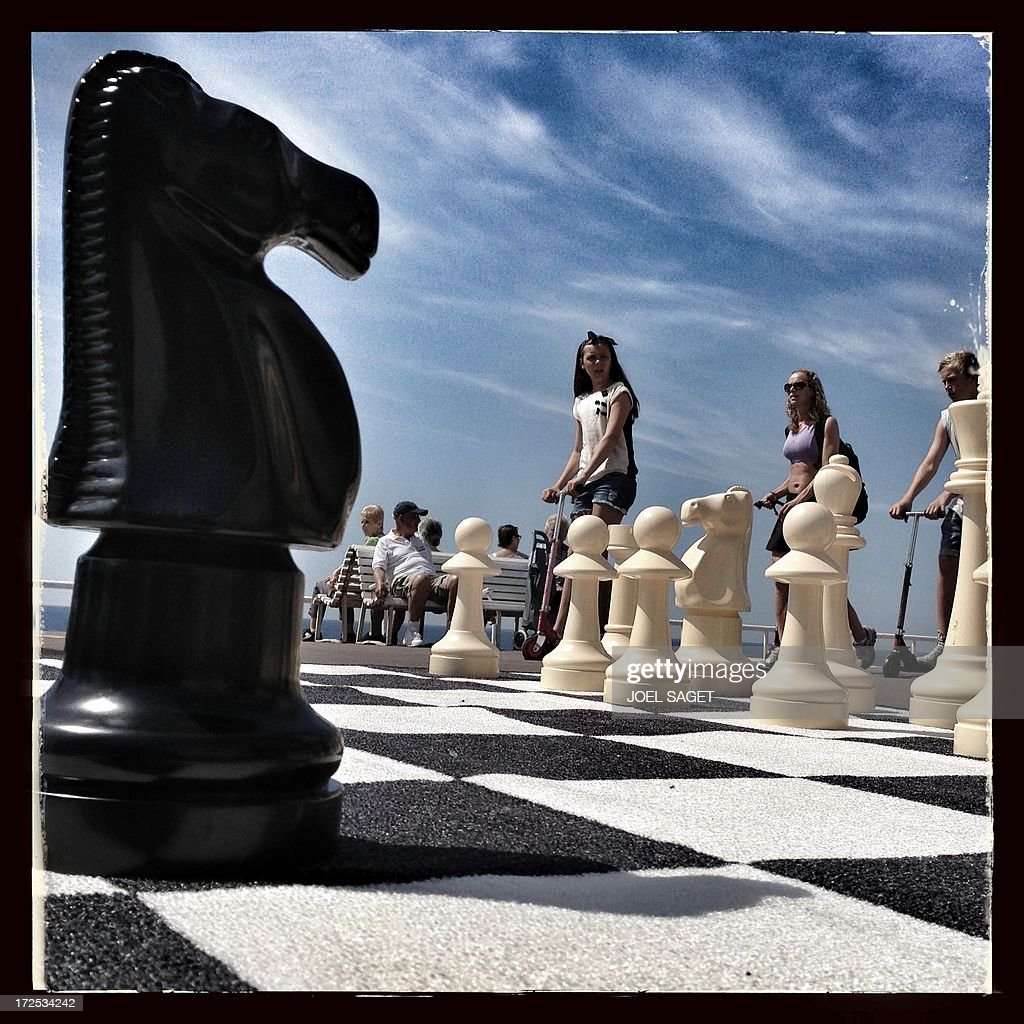 Image taken with a mobile phone shows a giant chessboard on the Promenade des Anglais in the French southeastern city of Nice, before the start of the 25 km team time-trial and fourth stage of the 100th edition of the Tour de France cycling race on July 2, 2013 around Nice.