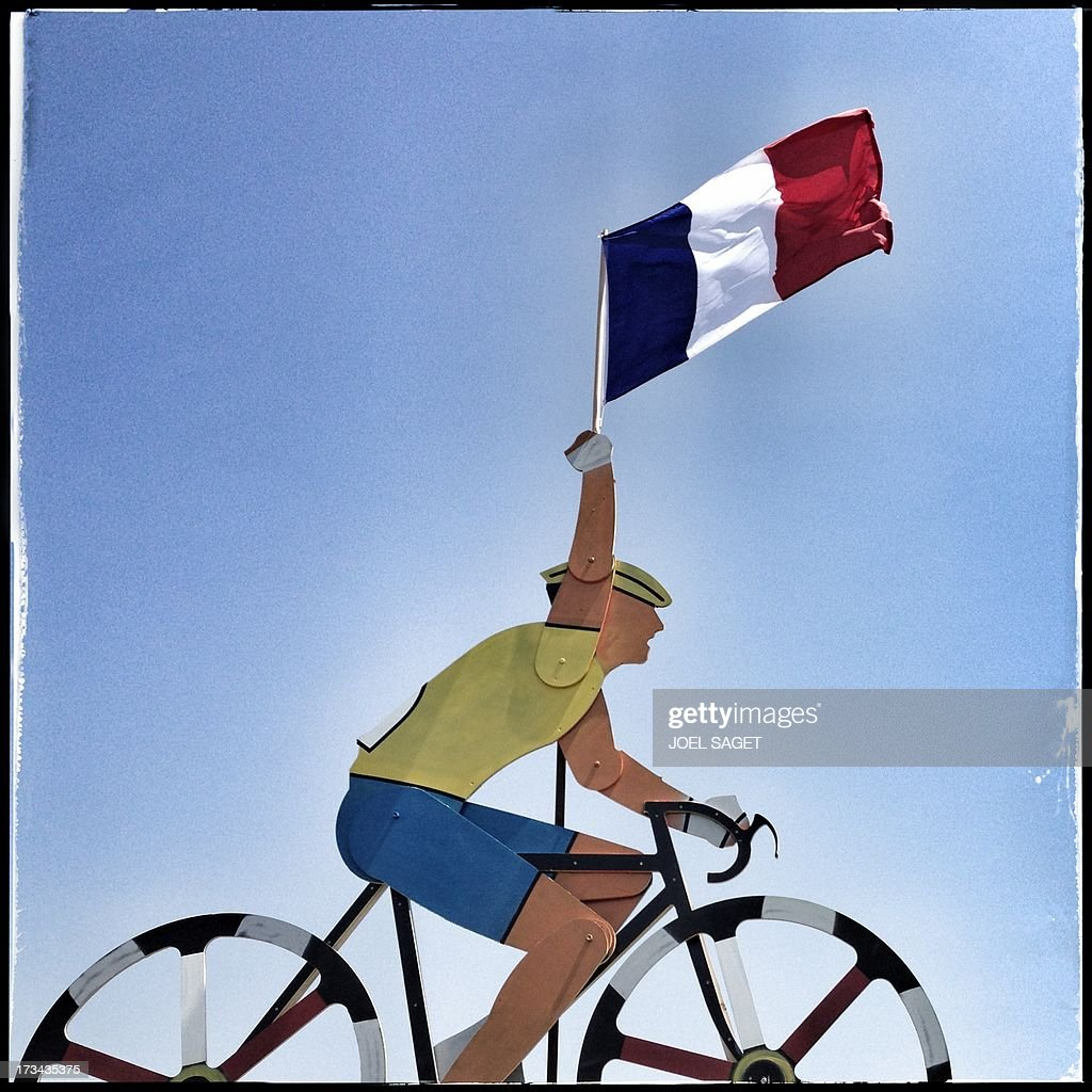 Image taken with a mobile phone shows a life-sized silhouette of cyclist holding a French national flag seen along the road during the 173 km thirteenth stage of the 100th edition of the Tour de France cycling race on July 12, 2013 between Tours and Saint-Amand-Montrond, central France.