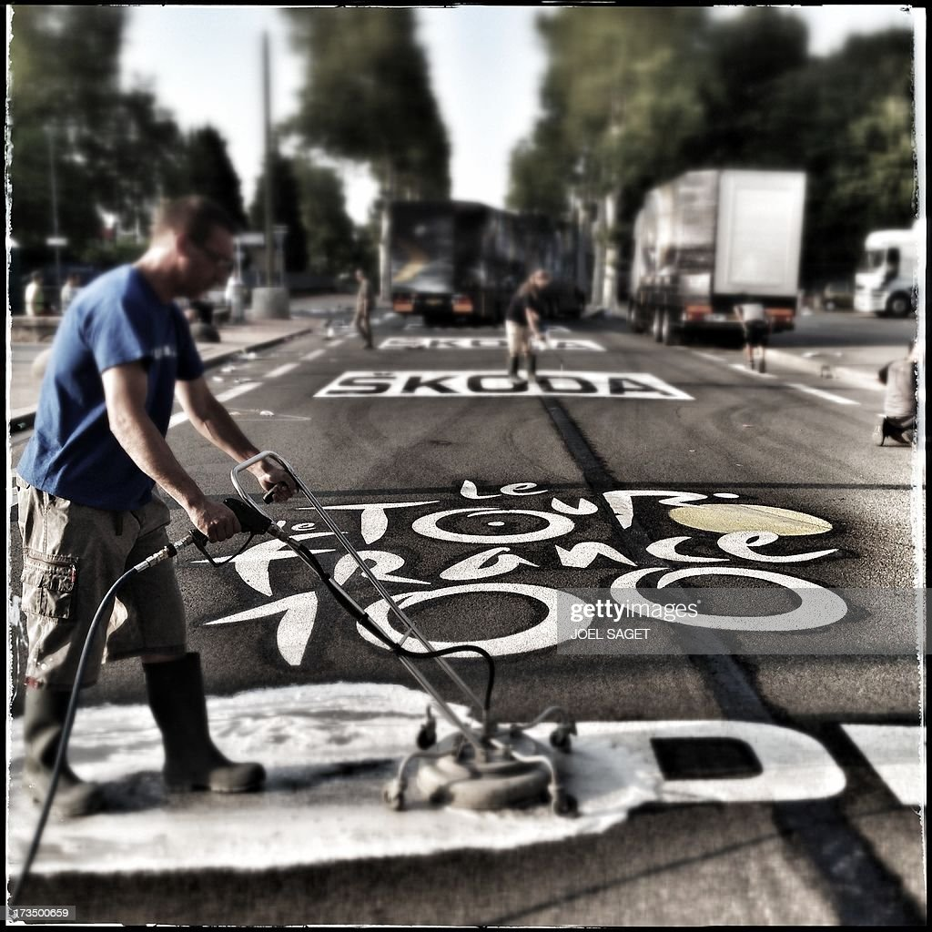 Image taken with a mobile phone shows a man removing an inscription reading the 'Tour de France 100th'on the road near the finish line at the end of the191 km fourteenth stage of the 100th edition of the Tour de France cycling race on July 13, 2013 between Saint-Pourcain-sur-Sioule and Lyon, central eastern France.