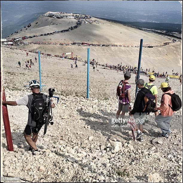 Image taken with a mobile phone shows supporters walking on the Mont Ventoux near the finish line at the end of the 2425 km fifteenth stage of the...