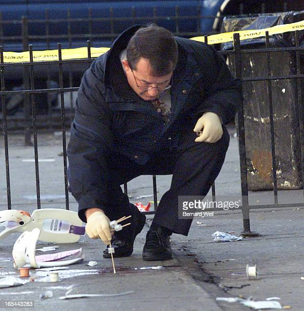 An officer from ident takes a blood sample outside the front entrance to Spin Cat an all night dance club on Isabella St at Yonge St Toronto March 4...