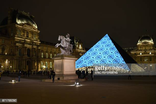 Images are projected onto the Louvre Pyramid in Paris at night on November 8 2017 to mark the opening of the Louvre Abu Dhabi Museum on Saadiyat...