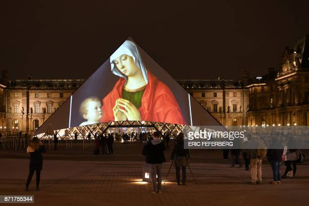 TOPSHOT Images are projected onto the Louvre Pyramid in Paris at night on November 8 2017 to mark the opening of the Louvre Abu Dhabi Museum on...