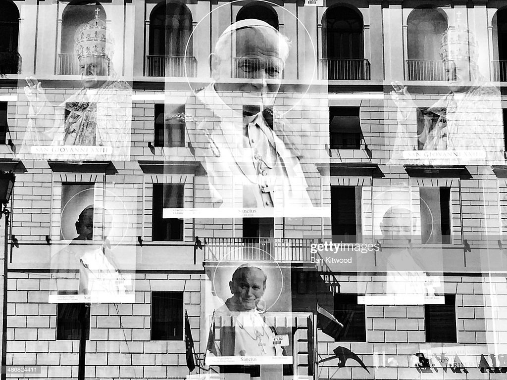 Images depicting the late Pope John Paul II and Pope John XXIII hang in a shop window near St Peter's basilica on April 25, 2014 in Vatican City, Vatican. Dignitaries, heads of state and Royals, from Europe and across the World, are gathering in the Vatican ahead of tomorrow's canonisations. The late Pope John Paul II and Pope John XXIII will be canonised on Sunday 27 April, inside the Vatican when 800,000 pilgrims from around the world are expected to attend.