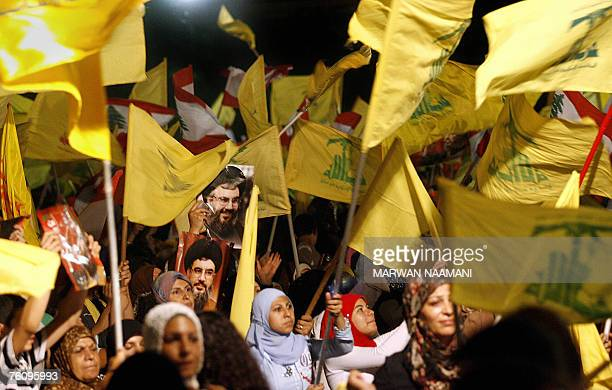 Images of Hezbollah chief Hassan Nasrallah are seen among scores of Hezbollah and Lebanese national flags being waved by Hezbollah supporters during...