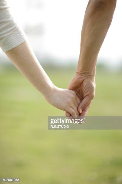 Images of middle-aged men and middle-aged women holding hands