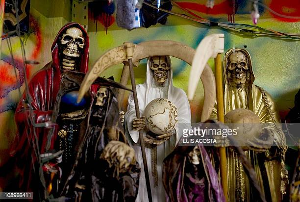 Images of the 'Santa Muerte' are seen at the shrine in honour of the goddess at the Iztapalapa shantytown in Mexico City on February 4 2011 The cult...