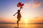imagination, happy girl jumping with multicolored balloons at sunset on the beach, fly, follow your dream