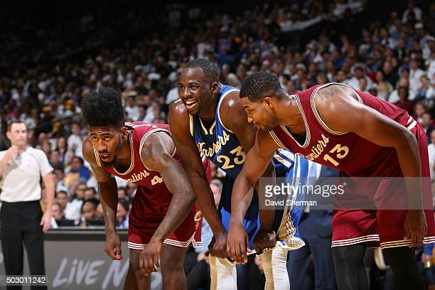 Iman Shumpert and Tristan Thompson of the Cleveland Cavaliers look to box out Draymond Green of the Golden State Warriors on December 25 2015 at...