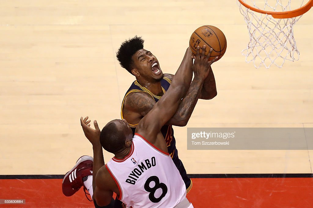 Iman Shumpert of the Cleveland Cavaliers drives to the basket in the first half and is fouled by Bismack Biyombo of the Toronto Raptors in game four...