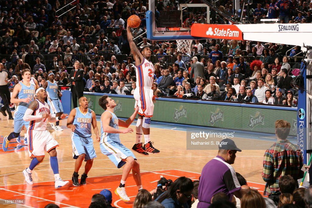 Iman Shumpert of the New York Knicks goes in for a dunk as Danilo Gallinari of the Denver Nuggets watches during the game on January 21 2012 at...