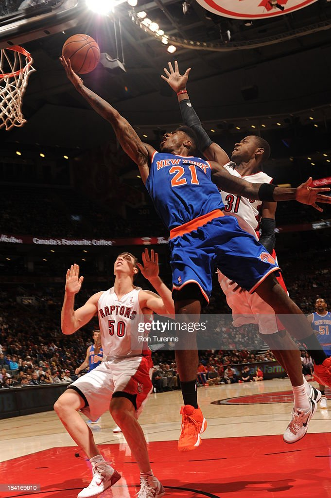 <a gi-track='captionPersonalityLinkClicked' href=/galleries/search?phrase=Iman+Shumpert&family=editorial&specificpeople=5042486 ng-click='$event.stopPropagation()'>Iman Shumpert</a> #21 of the New York Knicks shoots a layup against <a gi-track='captionPersonalityLinkClicked' href=/galleries/search?phrase=Tyler+Hansbrough&family=editorial&specificpeople=642794 ng-click='$event.stopPropagation()'>Tyler Hansbrough</a> #50 of the Toronto Raptors during the game on October 11, 2013 at the Air Canada Centre in Toronto, Ontario, Canada.