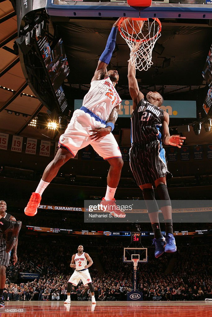 Iman Shumpert #21 of the New York Knicks slam dunks over Maurice Harkless #21 of the Orlando Magic during a game at Madison Square Garden in New York City on December 6, 2013.