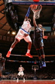 Iman Shumpert of the New York Knicks slam dunks over Maurice Harkless of the Orlando Magic during a game at Madison Square Garden in New York City on...