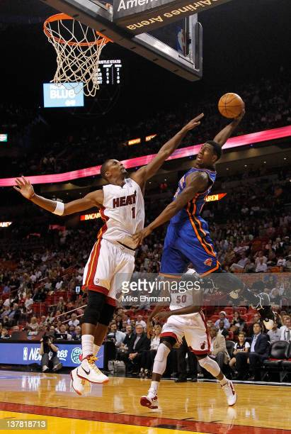 Iman Shumpert of the New York Knicks tries to dunk over Chris Bosh of the Miami Heat during a game at American Airlines Arena on January 27 2012 in...