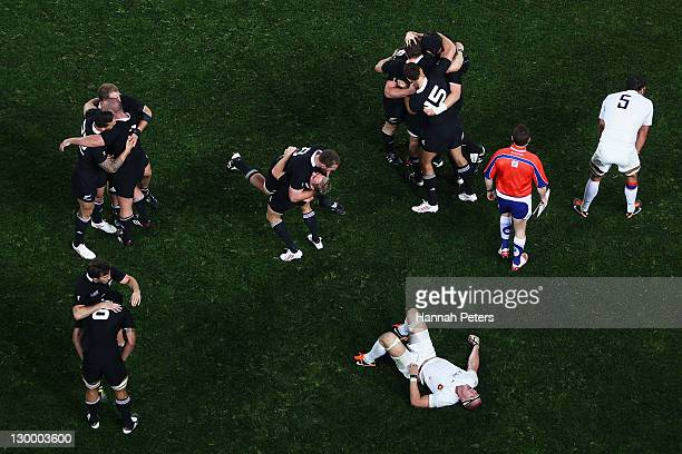 Imanol Harinordoquy of France lies dejected as the All Blacks celebrate winning the 2011 IRB Rugby World Cup Final match between France and New...