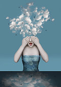 Beautiful surreal image with a girl who covers her eyes with the clouds coming out of his head