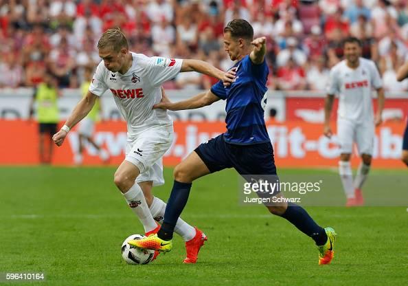 Immanuel Hoehn of Darmstadt tackles Artjoms Rudnevs of Cologne during the Bundesliga match between 1 FC Koeln and SV Darmstadt 98 at...