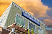 Immediate Care Sign Above Windows Outside Hospital or Emergency Clinic Building Against Sky with Clouds