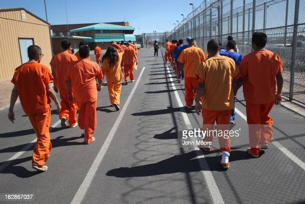 Immigrant detainees walk through the Immigration and Customs Enforcement detention facility on February 28 2013 in Florence Arizona With the...
