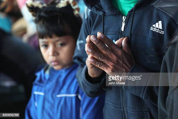 Immigrant families pray at a Catholic Charities sponsored 'immigrant respite center' before taking a bus from the border into the interior of the...