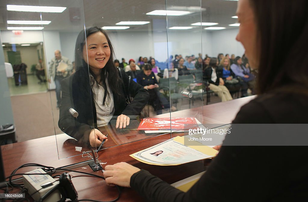 Immigrant from China Joy Bixia smiles after signing a naturalization certificate to become an American citizen at the district office of U.S. Citizenship and Immigration Services (USCIS) on January 28, 2013 in Newark, New Jersey. Some 38,000 immigrants became U.S. citizens at the Newark office alone in 2012.