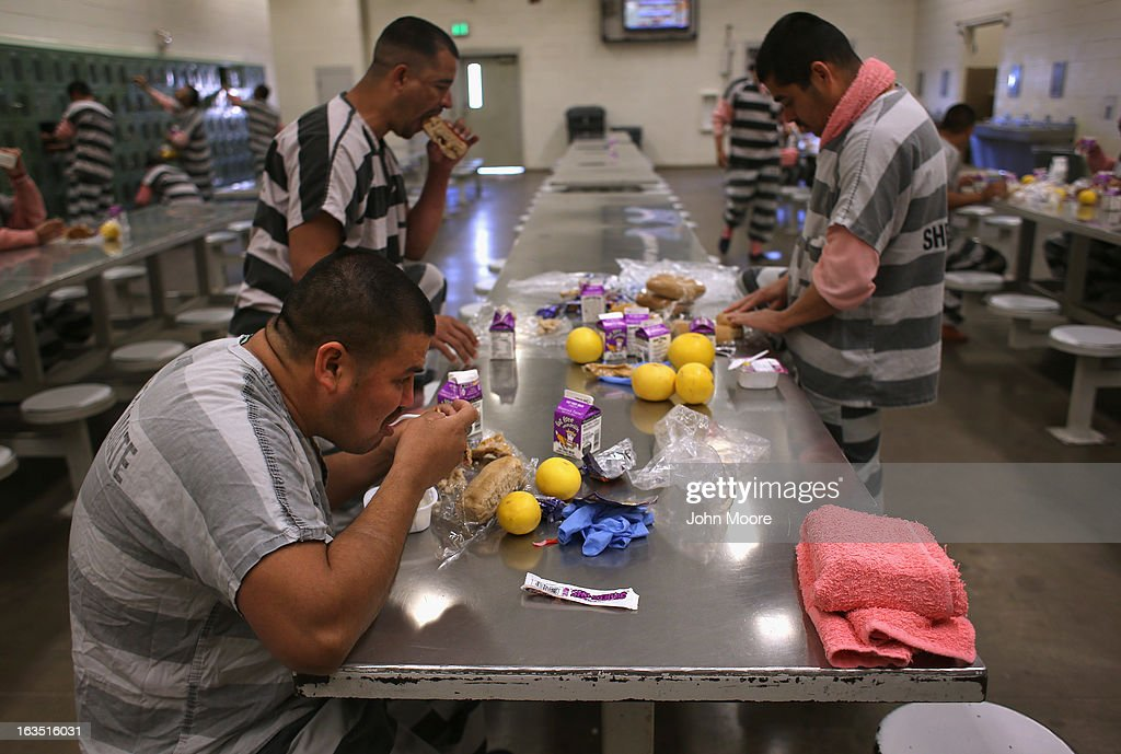 Immigrant inmates eat breakfast at the Maricopa County Tent City jail on March 11, 2013 in Phoenix, Arizona. The striped uniforms and pink undergarments are standard issue at the facility. The tent jail, run by Maricopa County Sheriff Joe Arpaio, houses undocumented immigrants who are serving up to one year after being convicted of crime in the county. Although many of immigrants have lived in the U.S for years, often with families, most will be deported to Mexico after serving their sentences.
