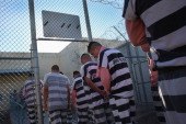 Immigrant inmates line up for breakfast at the Maricopa County Tent City jail on March 11 2013 in Phoenix Arizona Striped uniforms and pink...