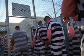 Immigrant inmates line up for breakfast at the Maricopa County Tent City jail on March 11 2013 in Phoenix Arizona The striped uniforms and pink...