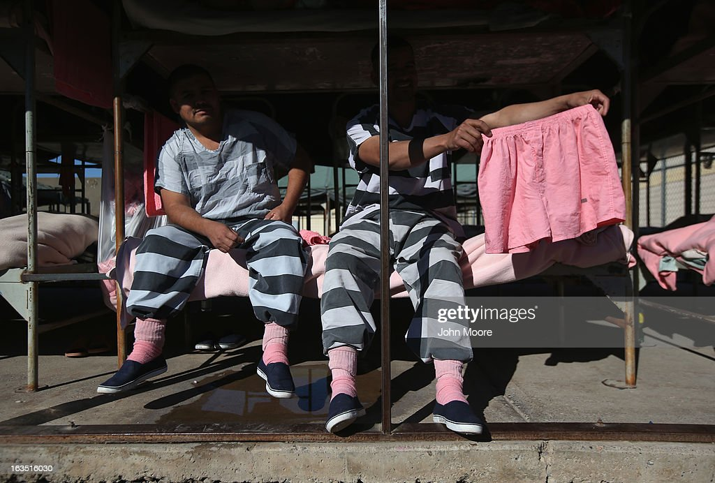 Immigrant inmates show off a pair of pink underwear while sitting on a bunk in the Maricopa County Tent City jail on March 11, 2013 in Phoenix, Arizona. The striped uniforms and pink undergarments are standard issue at the facility. The tent jail, run by Maricopa County Sheriff Joe Arpaio, houses undocumented immigrants who are serving up to one year after being convicted of crime in the county. Although many of immigrants have lived in the U.S for years, often with families, most will be deported to Mexico after serving their sentences.
