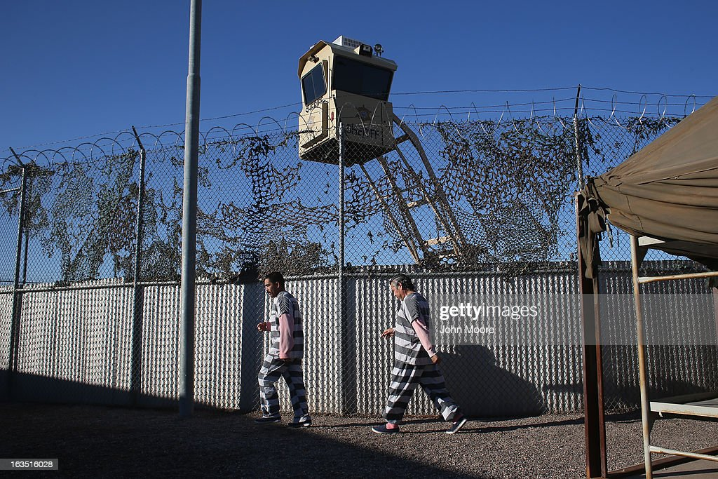 Immigrant inmates walk for excercise at the Maricopa County Tent City jail on March 11, 2013 in Phoenix, Arizona. The striped uniforms and pink undergarments are standard issue at the facility. The tent jail, run by Maricopa County Sheriff Joe Arpaio, houses undocumented immigrants who are serving up to one year after being convicted of crime in the county. Although many of immigrants have lived in the U.S for years, often with families, most will be deported to Mexico after serving their sentences.