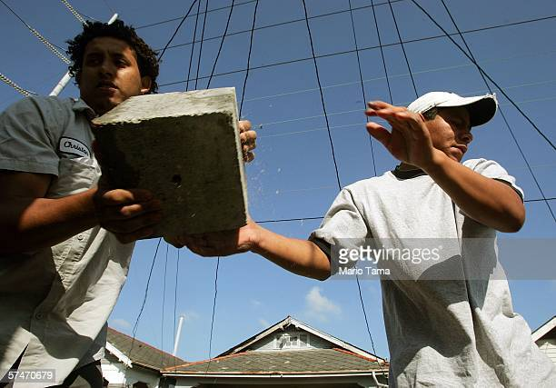 Immigrant laborers Jose from Mexico and Christian from Honduras perform 'house leveling' work on a home damaged by Hurricane Katrina April 27 2006 in...