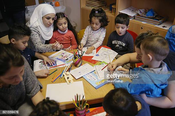 Immigrant mothers with their children look through games and books during the presentation of a new initiative to help children of refugees learn to...