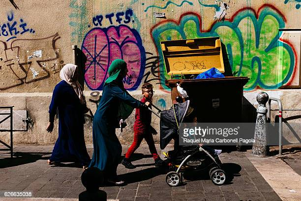 Immigrant muslim family walking on city center colourful street