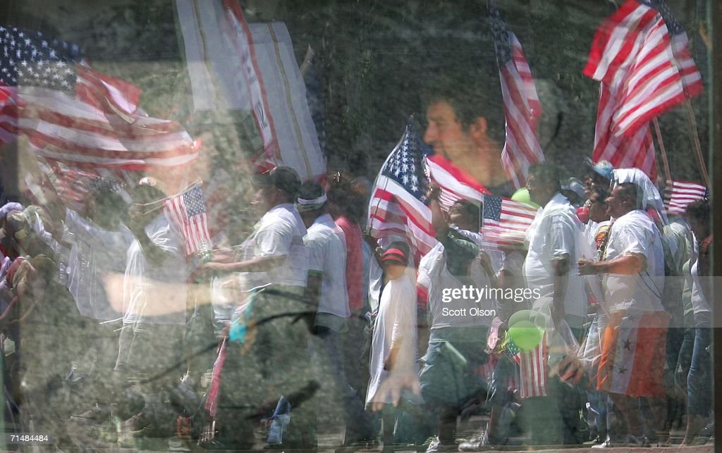 Immigrant rights demonstrators are reflected in a window in front of a construction worker as they march toward downtown July 19, 2006 in Chicago, Illinois. About 10,000 people marched from the city?s west side, through downtown, to Grant Park calling for a halt to deportations while Congress works on an immigration reform package.