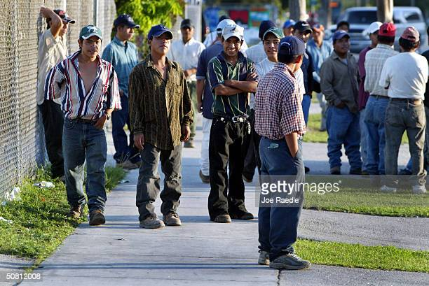 Immigrant workers crowd together as they wait for people looking for day laborers May 7 2004 in Homestead Florida Congressional Democrats rallied May...