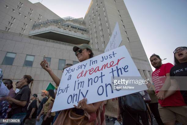 Immigrants and supporters march past the Metropolitan Detention Center as undocumented people jailed inside tap on the windows in opposition to the...