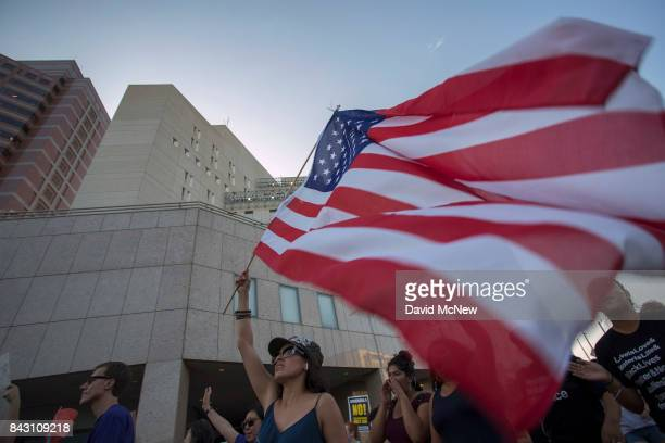 Immigrants and supporters march past the Metropolitan Detention Center as undocumented people jailed inside tap on the windows in opposition to...