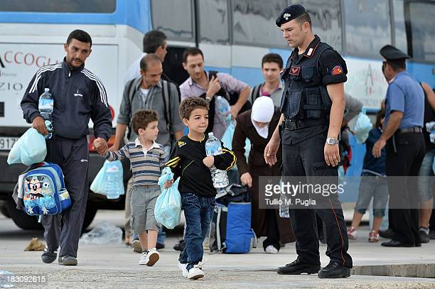 Immigrants board a ship bound for Porto Empedocle Sicily on October 4 2013 in Lampedusa Italy The search for bodies continues off the coast of...