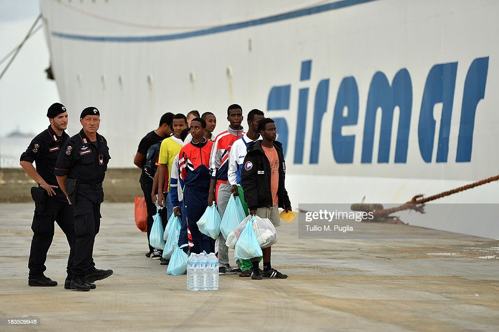 Immigrants board a ship bound for Porto Empedocle, Sicily on October 7, 2013 in Lampedusa, Italy. The search for bodies continues off the coast of Southern Italy as the death toll of African migrants who drowned as they tried to reach the island of Lampedusa is expected to reach over 300 people. The tragedy has bought fresh questions over the thousands of asylum seekers that arrive into Europe by boat each year.
