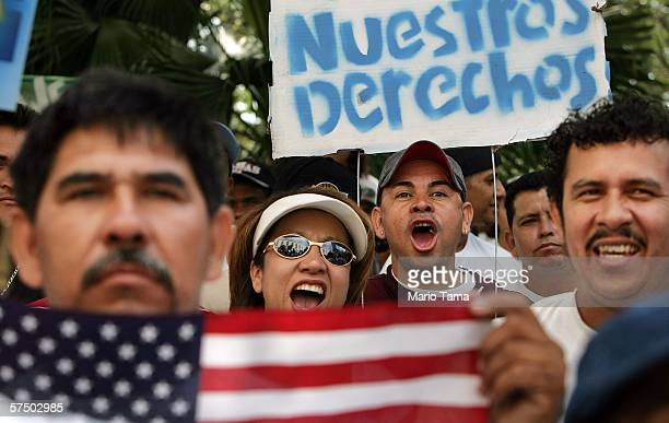 Immigrants cheer beneath a sign in Spanish reading 'Our Rights' at an immigrants rights rally and march May 1 2006 in New Orleans Louisiana...