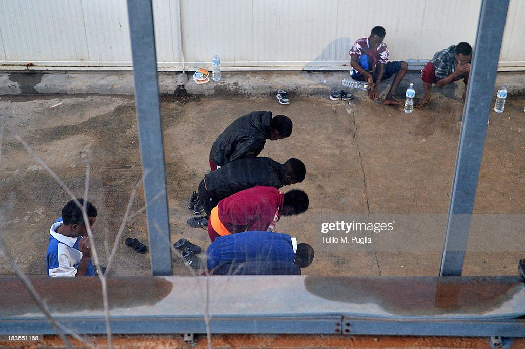 Immigrants detained after their arrival sit in the temporary shelter Center (CTP) on October 8, 2013 in Lampedusa, Italy. The search for bodies continues off the coast of Southern Italy as the death toll of African migrants who drowned as they tried to reach the island of Lampedusa is expected to reach over 300 people. The tragedy has bought fresh questions over the thousands of asylum seekers that arrive into Europe by boat each year.