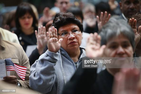 Immigrants from 25 countries take the oath of citizenship during a naturalization ceremony in Daley Plaza on September 16 2014 in Chicago Illinipois...