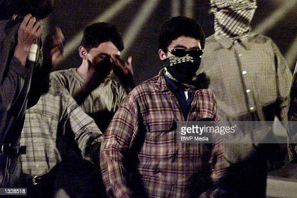 Immigrants from a refugee camp cross the bridge over the Eurotunnel entrance September 4 2001 in Sangatte France The masked man is believed to be a...