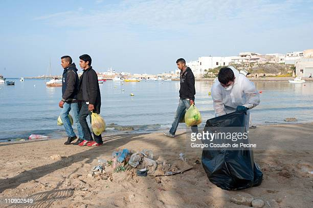 Immigrants from Tunisia walk on the beach near the sea port while an Italian volunteer cleans up rubbish on March 26 2011 in Lampedusa Italy A...