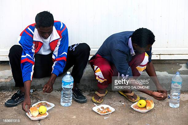 Immigrants have lunch at the 'Temporary Permanence Centre' a refugee camp in Lampedusa on October 8 2013 Divers in Italy resumed the grim search for...