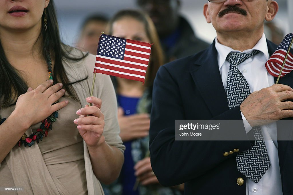 Immigrants hold American flags and listen to the national anthem during a naturalization ceremony at the district office of U.S. Citizenship and Immigration Services (USCIS) on January 28, 2013 in Newark, New Jersey. Some 38,000 immigrants became U.S. citizens at the Newark office alone in 2012.
